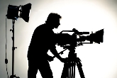 Searchlight and silhouette of the camera and cameraman.
